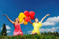 Girls holding balloons against sky