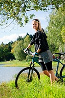 Beautiful young blond woman riding bicycle by lake summer day