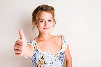 Portrait of a beautiful young blond showing thumbs up.