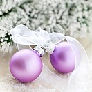 two christmas ornaments with ribbon and fir in background