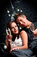 Young extravagant man and woman with champagne sitting in front of silver decorated Christmas tree