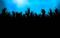 Silhouette of a crowd with raised hands, either at a concert or on the dance floor in a club.