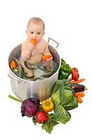 Beautiful young baby in a pan with vegetables