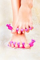 body part shot of beautiful healthy young woman´s feet in pedicure toe separators on white fur