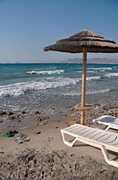 beautiful beach with umbrella and chairs in Kos, Greece Turkey on the background