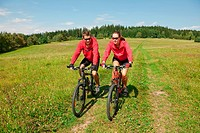 Young couple riding mountain bike in spring meadow nature on sunny day