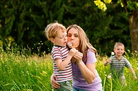 Little boy and his mother blowing dandelion seed for a wish on a meadow outdoors in summer, in the background his brother is running