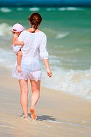 Rear view of young mother and her little daughter on tropical white sand beach