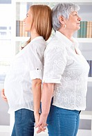 Pregnant woman and senior mother standing back_to_back, holding hands, smiling.