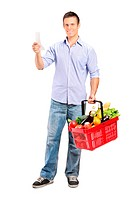 Full length portrait of a man looking at store receipt and holding a shopping basket isolated on white background