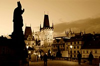 An evening view of the beautiful gothic architecture at the end of Charles Bridge on the Malá Strana side. Prague castle in the background.