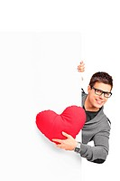 Young male holding a red heart shaped pillow and a blank banner isolated on white background