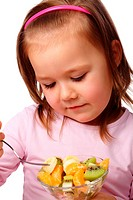 Cute little girl eats fruit salad using fork, isolated over white