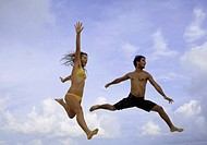young couple jumping in the air at a hawaii beach