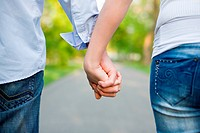 Closeup shot of young couple holding hands.