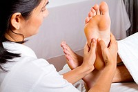 asian masseuse giving professional foot massage