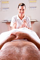 customer point of view of professional masseuse giving foot massage to male customer