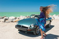 Portrait of a 57 year old woman standing by her MG car at a beach
