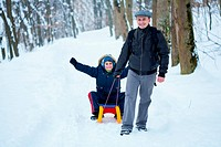 Father and son with a sledge outdoor in the snow