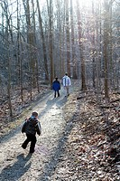 A young boy runs to catch up to his Father and older brother on a wooded trail