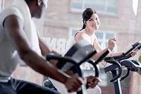 Two people speaking together while biking at health club, foucs on the girl
