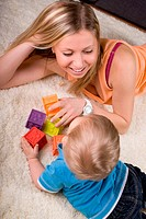 Young mother playing with baby boy  1 year old  at home.