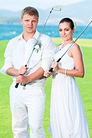 Bride and groom are playing golf at wedding day