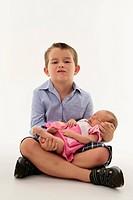 Mischievous boy holding newborn baby sister.