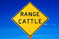 range cattle sign with bullet holes and blue sky