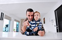 portrait of a happy father and son together in modern living room home indoor