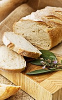 Freshly baked loaf of bread, just sliced with fresh herbs.