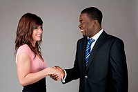 Smiling young woman and African American business man shaking hands.