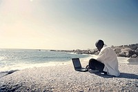African young man using a laptop at the seaside