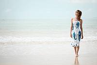Young woman walking on wet sand on a beach