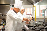Two cooks preparing food in a restaurant kitchen