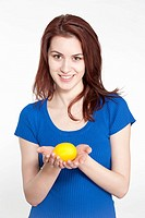 Studio shot of a young woman holding a lemon