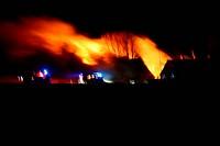 house on fire at night. blaze of flames burn down farm