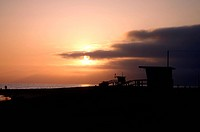 two Venice beach Lifeguard towers, beach truck, and people silhouettes at sunset in California.
