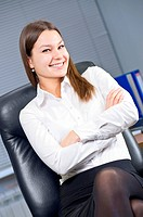 Attractive young caucasian brunette businesswoman sitting in her office