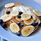 Pancakes topped with fresh blueberries, sliced banana and yogurt.
