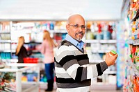 Smiling mature man shopping in the supermarket with people in the background