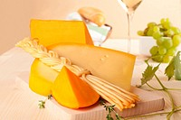 Cheese collection, pastry, white wine and grape in background. Luxurious food background.