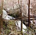 Snow covers the leaves and mountain as Laurel falls cascades over the mountain and lone hiker stands on bridge