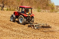 Red tractor on hill with disk harrow and rake
