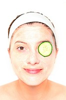 A picture of a young relaxed woman with her eye covered with cucumber