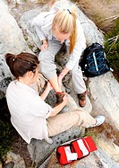 hiker with sprained ankle is helped by her friend with first aid kit for outdoor emergency