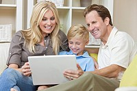 An attractive happy, young family of mother, father and son sitting on a sofa at home using a laptop computer