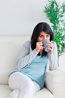 Woman drinking from a grey mug in a living room
