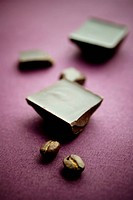 Chocolate with coffee beans on violet tablecloth