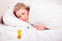 Sick blonde woman with a thermometer in her bed